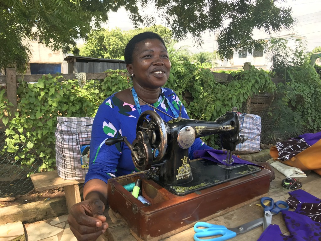 A seamstress sewing outside in Accra Ghana with her manual sewing machine
