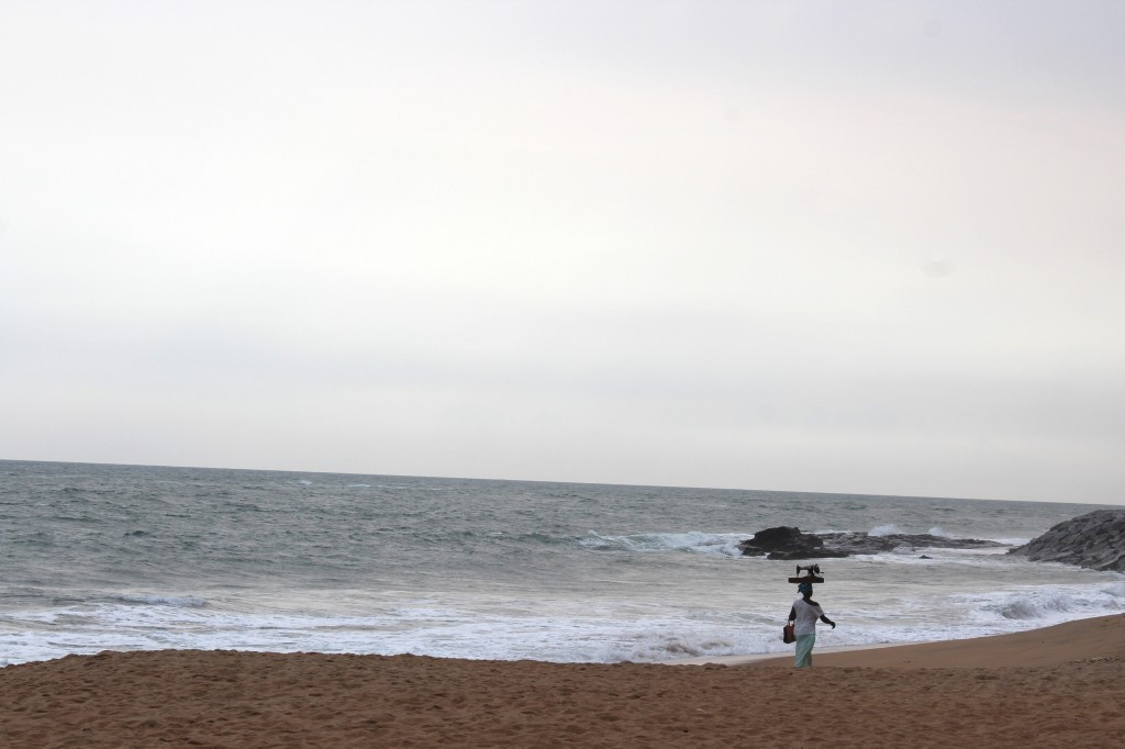 A lady with a sewing machine on her head walking along Elmina beach in Ghana