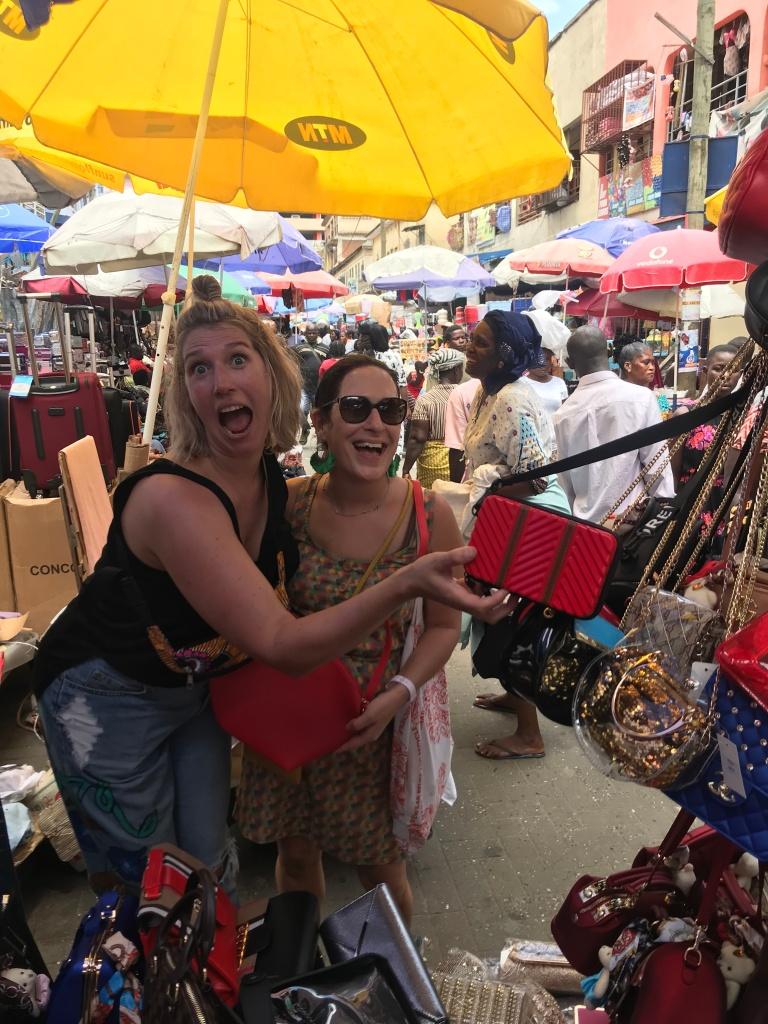 Shopping at Makola Market buying handbags from a vendor