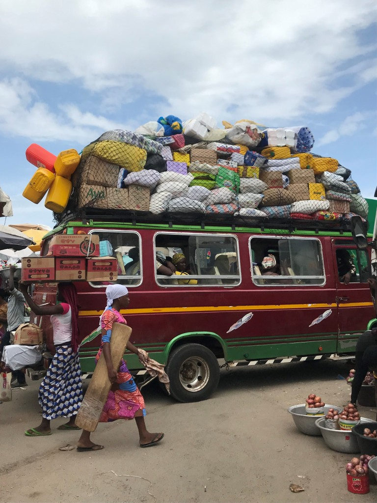A colourful tro tro loaded full of goods and passengers at Makola Market Accra