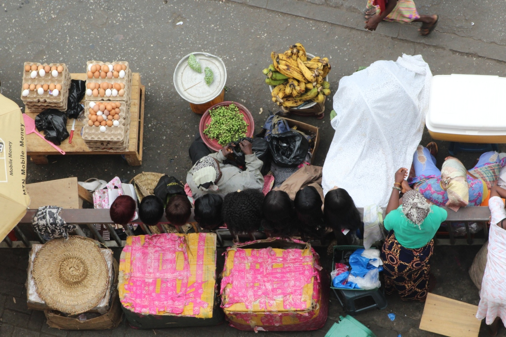A view of ladies selling wigs, eggs, plantain and okra at Makola Market Accra taken from the parking lot