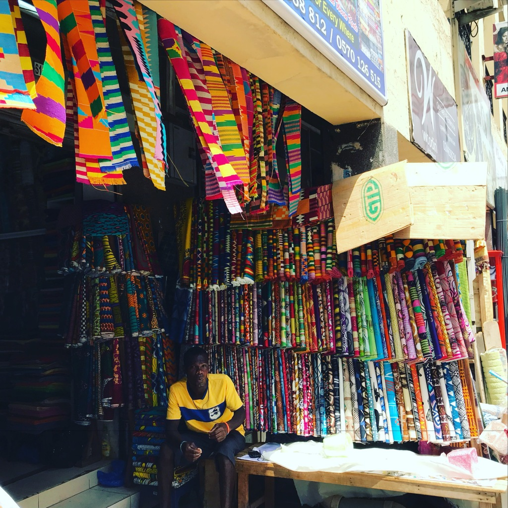 A fabric store selling African wax fabrics and Woodin and GTP fabrics. Kente cloth strips hang from the roof. Makola Market Accra