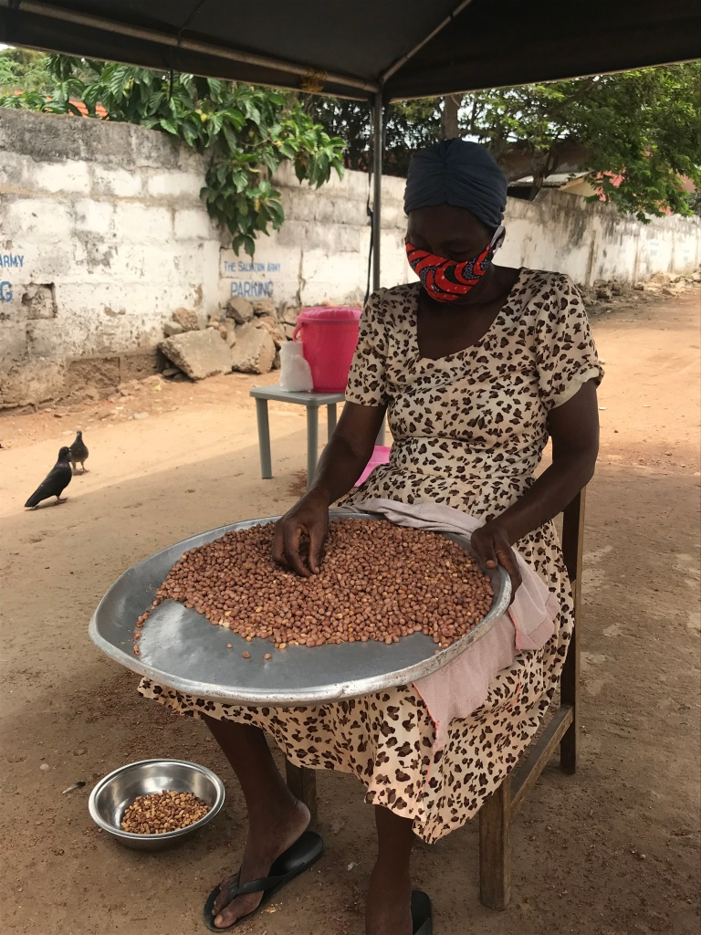 Ghanaian lady sorting ground nuts in Accra