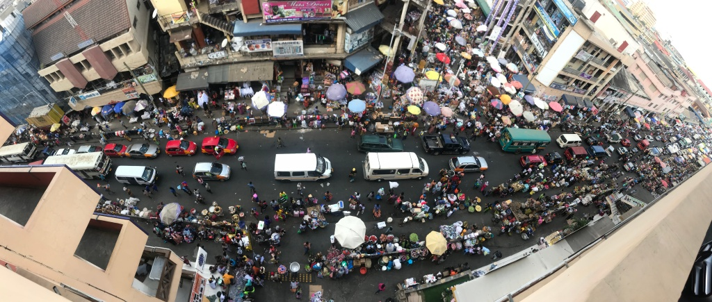 A panoramic view of Makola Market Accra taken from the car park with many vendors and cars below