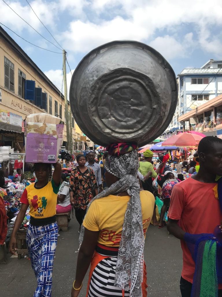 Kayayo girl in Accra carrying a silver bowl at Makola Market