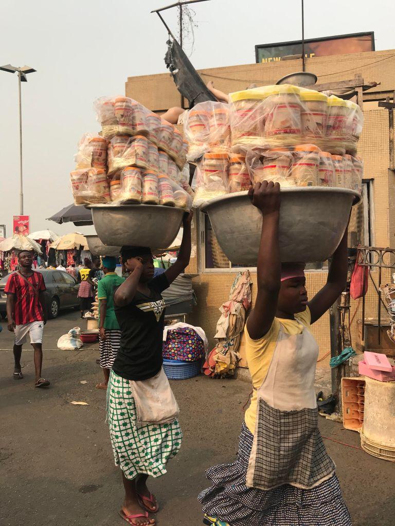 Kayayo girls (carrier girls) carrying heavy loads at Makola Market
