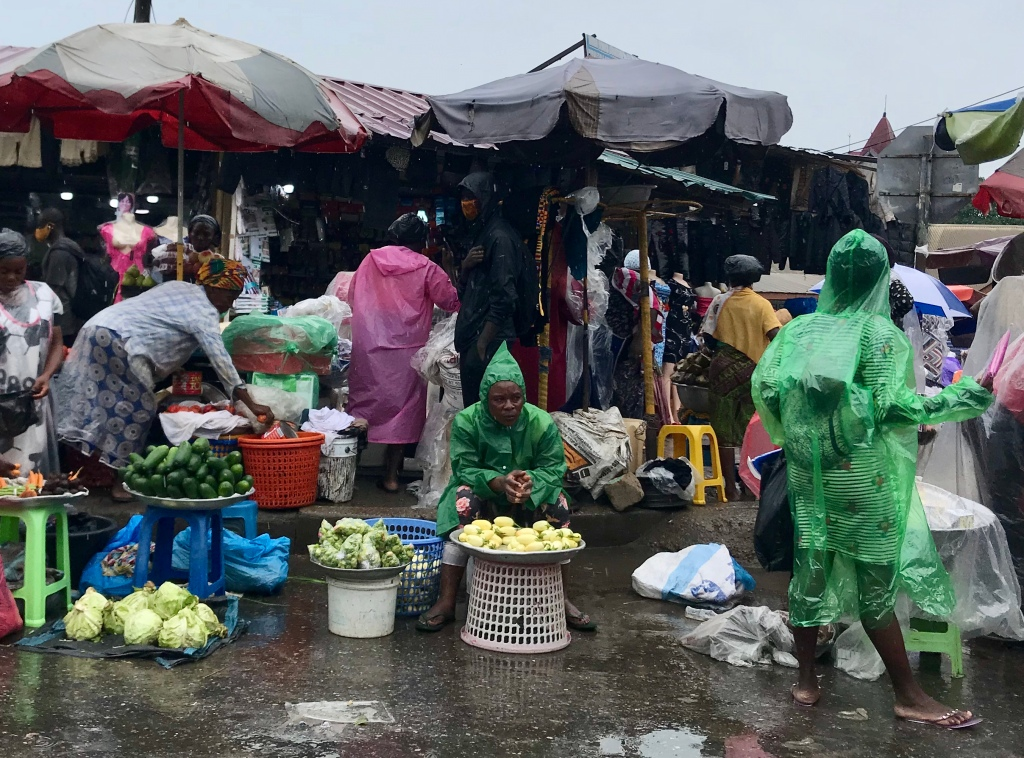 A rainy day in Accra, market vendors still sell vegetables in the rain and they are wearing raincoats.