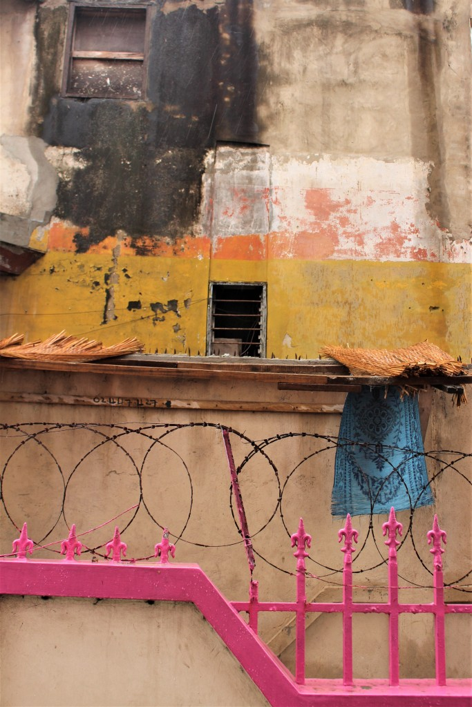 A colourful scene in old Accra, yellow and orange walls with bright pink spikes and a prayer mat hanging from a railing.