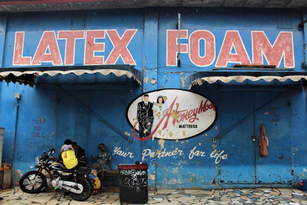 An old blue mural in old Accra, Honeymoon matress Your partner for Life is painted on the wall, and children play near a motorbike.