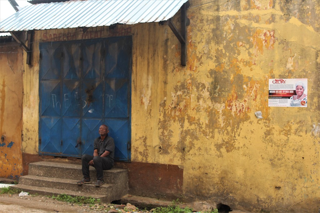 Old Accra, a man sits in front of a blue door and a yellow wall that is peeling from many layers of paint.